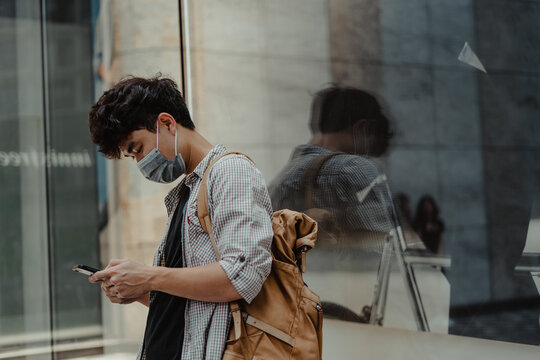 Asian man wearing surgical face mask using smart phone in outdoor.