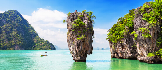 Travel photo of James Bond island with thai traditional wooden longtail boat in Phang Nga bay, Thailand. - fototapety na wymiar
