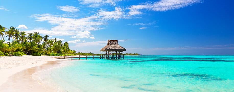 Panorama of beautiful gazebo on the tropical white sandy beach in Punta Cana, Dominican Republic.
