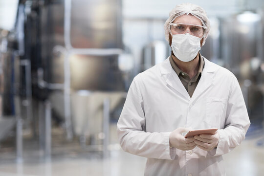 Waist up portrait of adult man working at chemical plant and looking at camera while wearing protective lab coat and mask, copy space