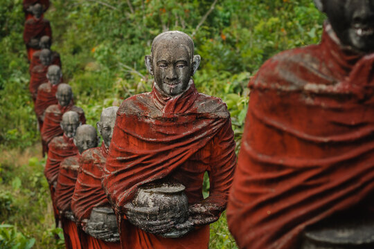 Hundreds of old statues of Buddhist monks collecting alms surround the Win Sein Taw Ya Buddha in Mawlamyine, Myanmar (Burma).