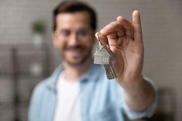 Obraz Satisfied homeowner. Blurred portrait of happy young man buyer renter of new modern home apartment holding key demonstrating wellbeing wealth celebrate achievement. Focus on hand with keys of dwelling - fototapety do salonu