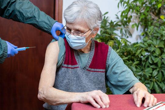 senior woman in nursing home receiving the vaccine