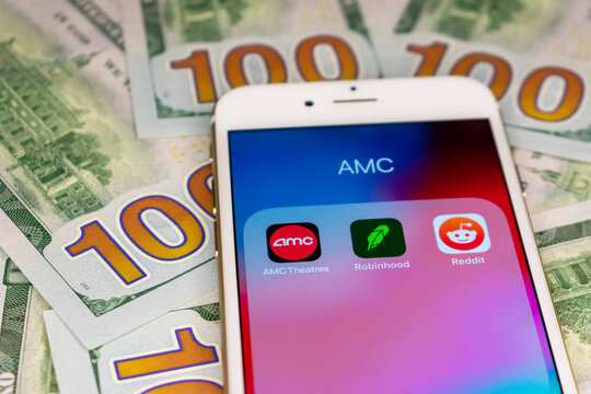 AMC Theatres, Robinhood and Reddit application icons grouped in AMC folder on smartphone. 100 dollars bills background. Selective focus. - San Jose, California, USA - March, 2021