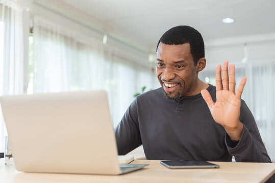 African American Freelancer waving hand while having video call with friends or family on laptop at home office. Black Male making online meeting and working on notebook.