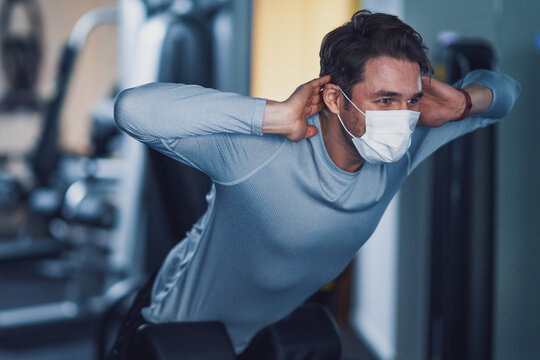 Adult man working out in a gym wearing mask