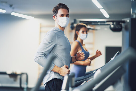 Two people working out on treadmill in masks