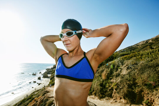 Young woman, triathlete in training in swimwear, swimhats and goggles on a beach.