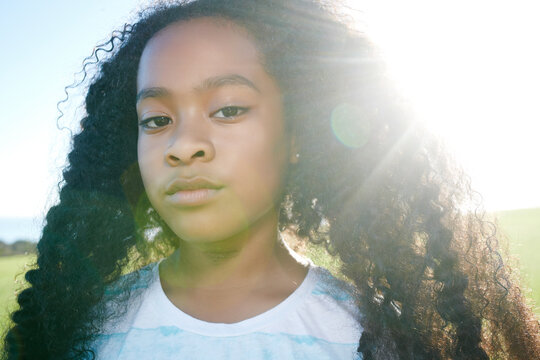 Young mixed race girl with long curly black hair with a serious expression