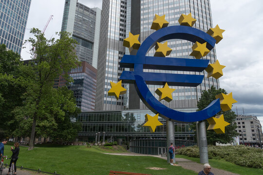 Frankfurt am Main, Germany - June 28, 2020: The Euro-Skulptur (German for Euro sculpture) set up in front of the European Central Bank, electronic signage showing a Euro sign and twelve stars around
