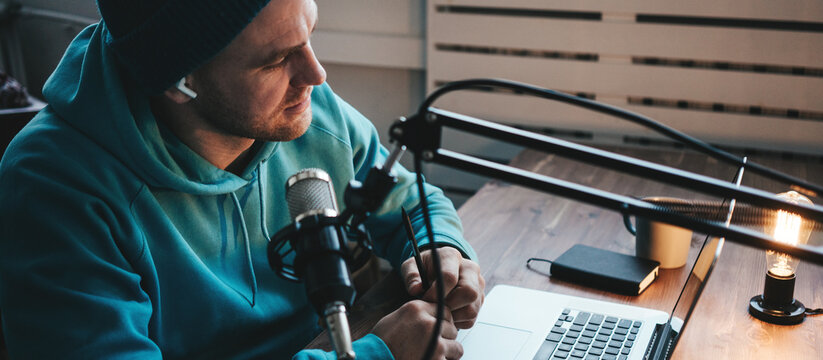 A man host streaming his audio podcast using microphone and laptop at his small broadcast studio