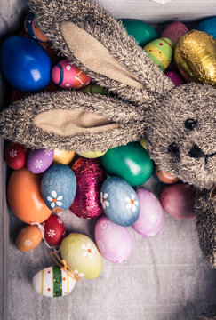 Easter greetings, postcard, greeting card with old vintage stuffed animal easter bunny with dark brown fur and many colorful easter eggs in the box. Long rabbit ears.