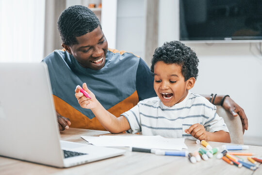African american father with his son is indoors at home helping doing homework