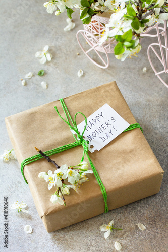 Mother's day or womens day background. Blooming cherry branch and a present with a congratulatory inscription that Happy Mother's Day on a gray stone table.