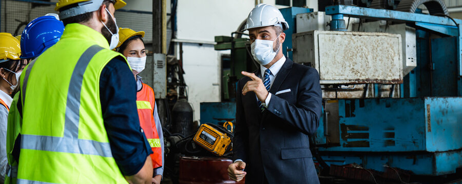 Industrial engineers and businessman in suite and safety helmet wearing mask working in factory, planning, discussing and training workers with tablet in metalwork place , teamwork and team concept