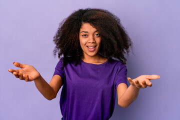 Young african american curly woman isolated on purple background makes scale with arms, feels happy...
