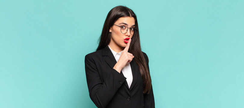 young pretty woman asking for silence and quiet, gesturing with finger in front of mouth, saying shh or keeping a secret. business concept