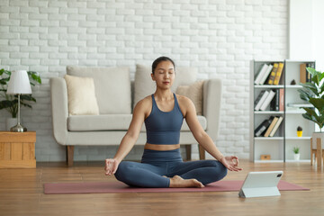 Athlete Asian indian woman looking laptop practice yoga lotus pose online course at home to...