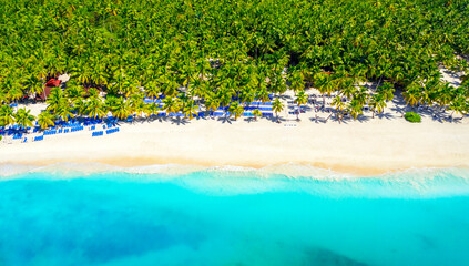 Paradise tropical island nature background. Top aerial drone view of beautiful beach with turquoise sea water and palm trees. Saona island, Dominican republic.