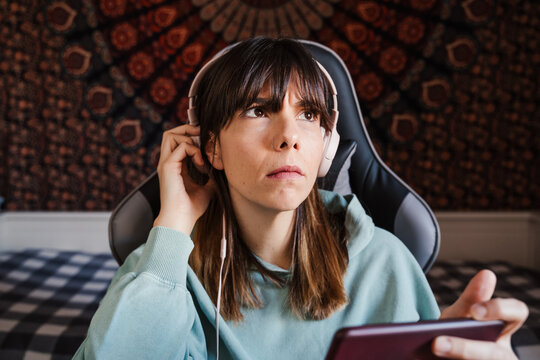 A beautiful woman listening to music on her phone while taking off her headphones to hear something. She is sitting on a chair in her bedroom holding her phone. Entertainment with technology concept
