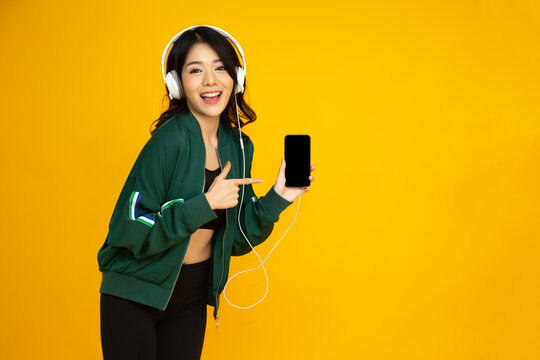 Asian fitness woman listening music with headphone on smartphone and pointing finger to phone isolated on yellow background