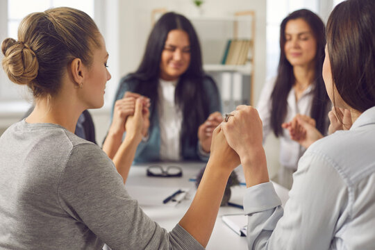 Unity concept. Team of happy young business women holding hands with eyes closed sitting together around office table in corporate group meeting. Value, respect, support and believe in your colleagues