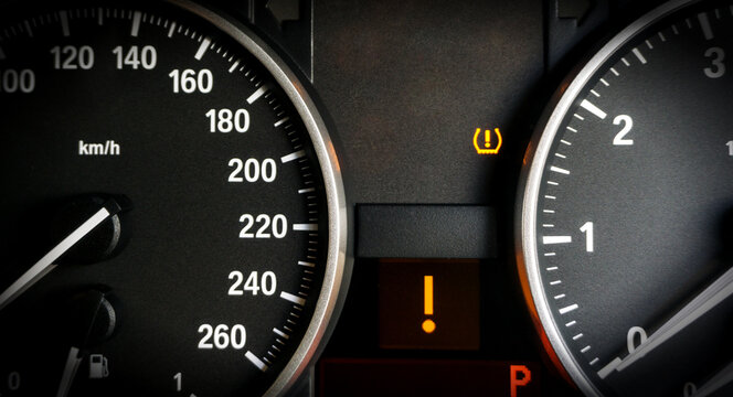 Closeup of lose tyre pressure alert in dashboard car on background.