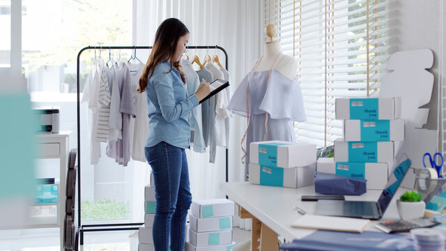 Young attractive beautiful hipster asia female fashion store owner use digital tablet check stock clothes or package box on rail rack at home office small SME business entrepreneur e-commerce concept.