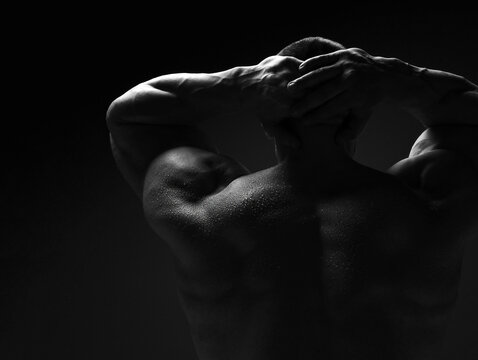 Strong muscular man, athlete, sportsman is standing naked, shirtless with his back to camera holding hands behind head over dark background