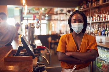 Portrait Of Female Bar Worker Wearing Face Mask During Health Pandemic Standing Behind Counter