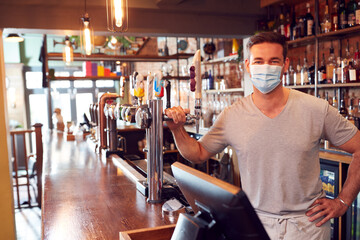Obraz Portrait Of Male Bar Worker Wearing Face Mask During Health Pandemic Standing Behind Counter - fototapety do salonu