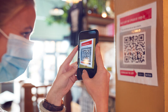 Woman In Mask With Mobile Phone Checking Into Venue Scanning QR Code During Health Pandemic