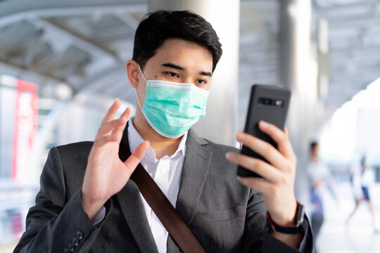 close up young Middle East business man stand outside and wear face mask while using video call form smartphone to talking with friends and family for new normal and healthy lifestyle concept