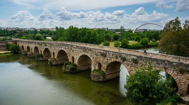 En primer término, el Puente Romano, más lejos la vegetación del río Guadiana y al fondo el Puente Lusitania de la ciudad de Mérida, España