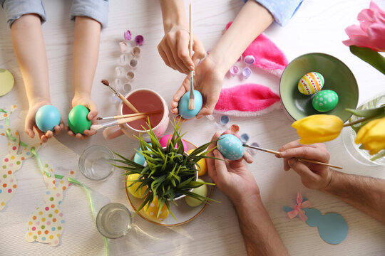 Father, mother and their child painting Easter eggs at white table, top view