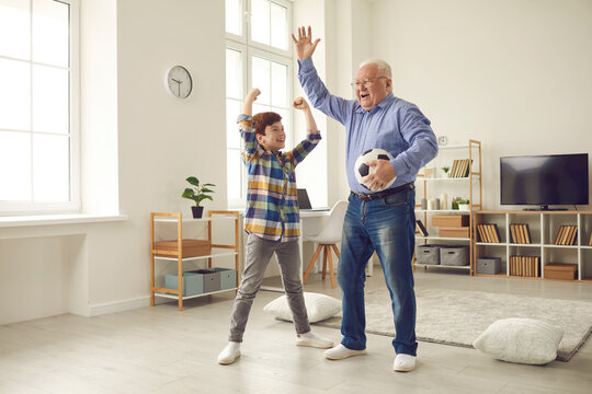 Happy football fans: Cheerful grandfather and excited teen grandson enjoying free time at home, having fun together, playing sports games and celebrating victory of their favorite team