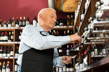 Attentive seller pouring wine from wine column in liquor store