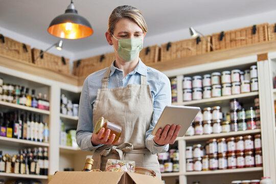 Female Owner Delicatessen With Digital Tablet Wearing Face Mask Preparing Online Grocery Order