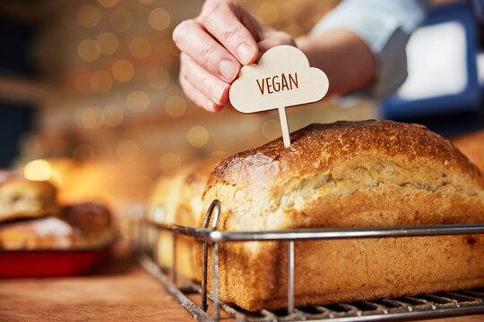 Sales Assistant In Bakery Putting Vegan Label Into Freshly Baked Baked Sourdough Loaves Of Bread