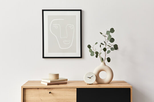 Stylish interior of living room with mock up poster frame, wooden commode, book, leaf in ceramic vase and elegant personal accessories. Minimalist concept of home decor. Template.