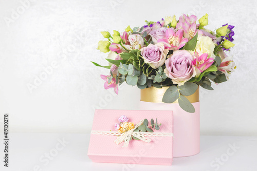 Beautiful bouquet of flowers in round box and pink gift box on a white table. Gift for holiday, birthday, Wedding, Mother's Day, Valentine's day, Women's Day. Floral arrangement in a hat box.