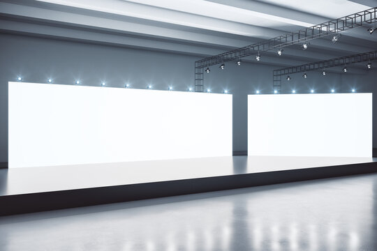 Two blank white boards behind black stage in urban style hall room with concrete floor and lights on top. Mockup