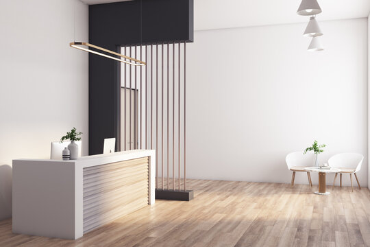Sunny modern style reception area in spacious office wth wooden furniture and floor, white walls and slatted screen