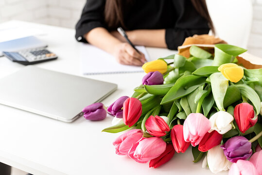 A young business woman florist writing in notebook or calendar at the office