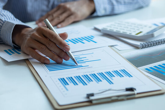 Financial Business man analyze the graph of the company's performance to create profits and growth, Market research reports and income statistics, Financial and Accounting concept.
