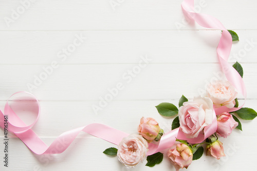 Floral frame with pink rose flowers , leaves , petals and ribbon. Template for greeting card  with empty space for Wedding, Valentine's day, Birthday, Mother's day, 8 march, women's day