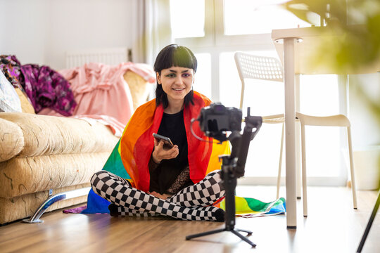 Gender fluid person wrapped in rainbow flag filming a vlog with camera