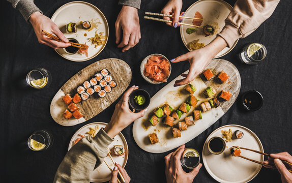 Family lockdown Japanese sushi dinner from delivery service at home. Flat-lay of table with salmon, crab, prawn, vegan rolls, wasabi, ginger and people eating together over dark background, top view