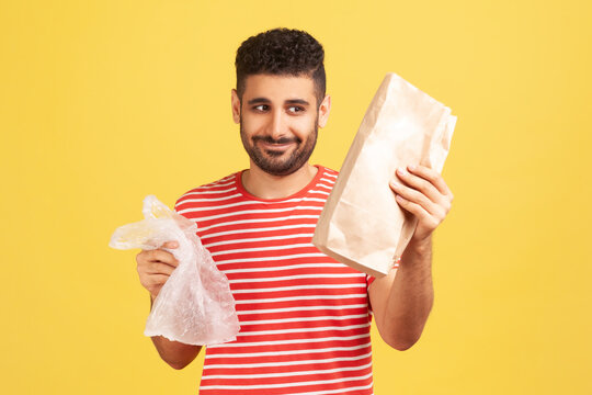 Happy cheerful man with beard in red striped t-shirt holding two bags in hands, looking at paper bag with smile, refusing to use plastic. Indoor studio shot isolated on yellow background