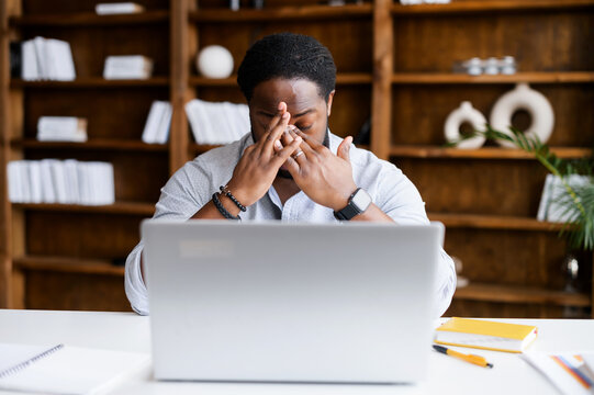 Overworked from online work on a laptop African-American man feeling eye strain, burnout, tired biracial male freelancer massaging bridge of the nose sitting at the workplace in a modern office space